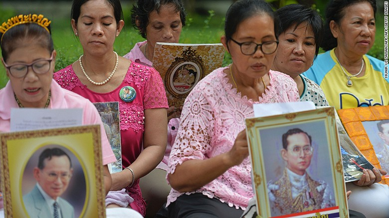 Women hold portraits of Thai King Bhumibol Adulyadej as they pray for his health at Siriraj Hospital, where the king is being treated, in Bangkok on October 12, 2016.