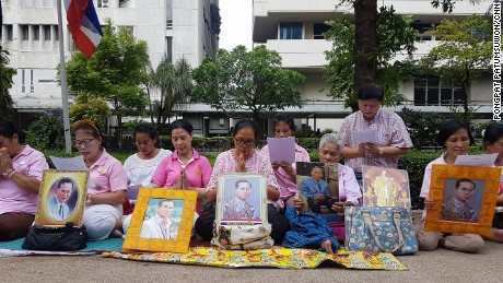 A group of women hold a vigil for King Bhumibol outside Siriraj Hospital.