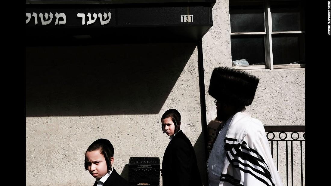 "Orthodox Jews walk through a neighborhood in Brooklyn, New York, during Yom Kippur on Wednesday, October 12. Yom Kippur --  also known as the ""Day of Atonement"" -- is one of the most sacred holidays and includes fasting, worshiping and atoning for sins from the past year."