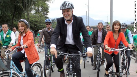 Colombian presidential candidate for the Green Alliance movement, former Bogota's mayor Enrique Penalosa (C), accompanied by his vice presidential partner Isabel Segovia (L), arrive bicycling to register their candidacy for the May 25 presidential election, in Bogota on March 26, 2014. Pe?alosa, elected on March 9 as a candidate of the Green Alliance in the inner query of this political movemnt, would be the opponent of president and candidate for reelection Juan Manuel Santos in a possible runoff in Colombia, according to the polls. AFP PHOTO/Felipe Caicedo        (Photo credit should read Felipe CAICEDO/AFP/Getty Images)