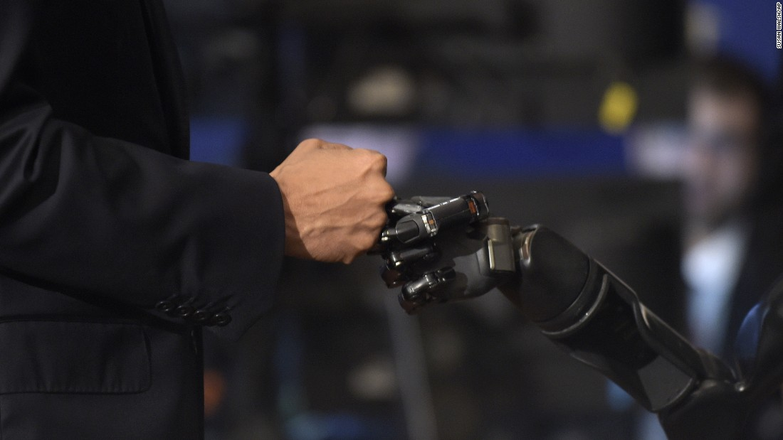 "President Barack Obama fist bumps with Nathan Copeland during the White House Frontiers Conference -- an event that explores the future of innovation around the globe -- in Pittsburgh, Pennsylvania, on Thursday, October 13. Copeland is paralyzed and uses a robotic arm controlled by a brain chip, which allows him to ""feel."""