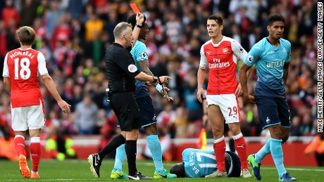 Referee Jonanthan Moss (L) shows Granit Xhaka a red card after his clumsy challenge.