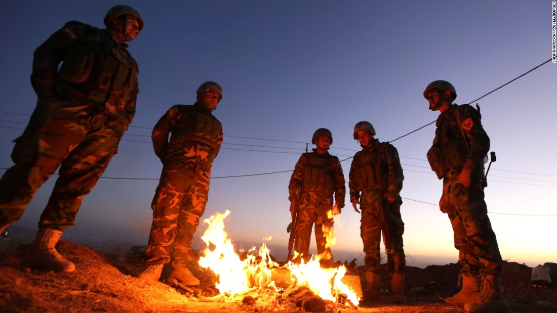 Members of the Iraqi coalition gather around a fire at Zardak mountain ahead of the offensive.