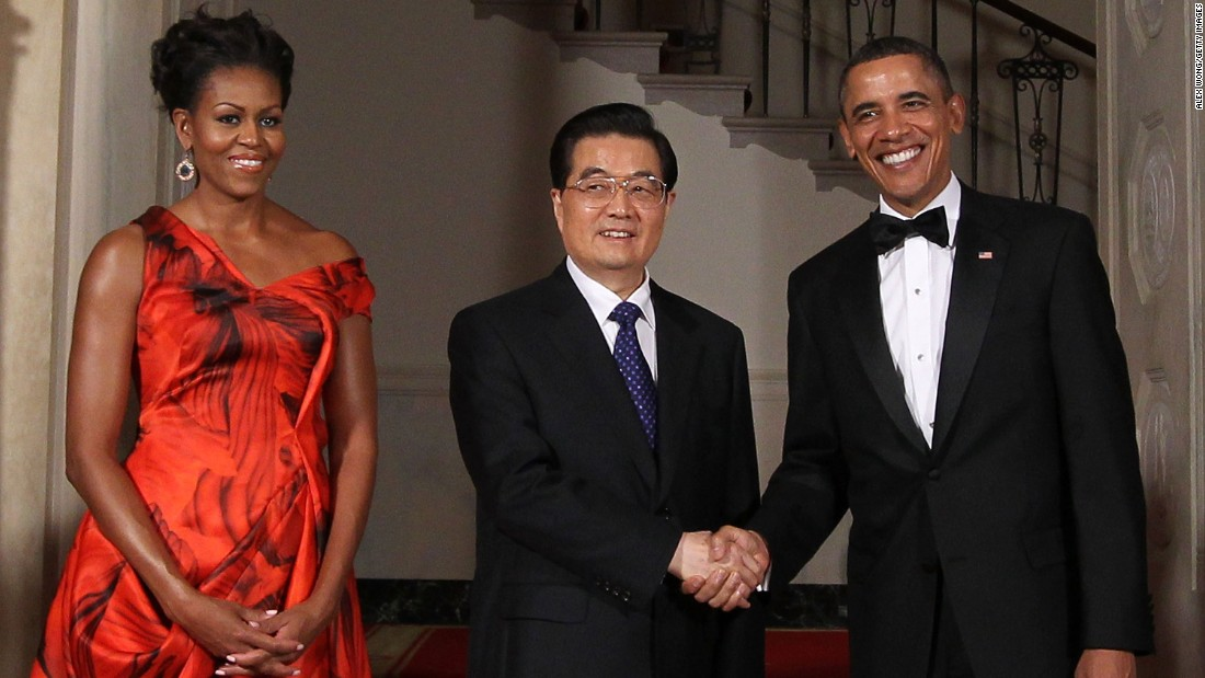 President Barack Obama shakes hands with Chinese President Hu Jintao as first lady Michelle Obama looks on at the Grand Staircase of the White House on January 19, 2011.