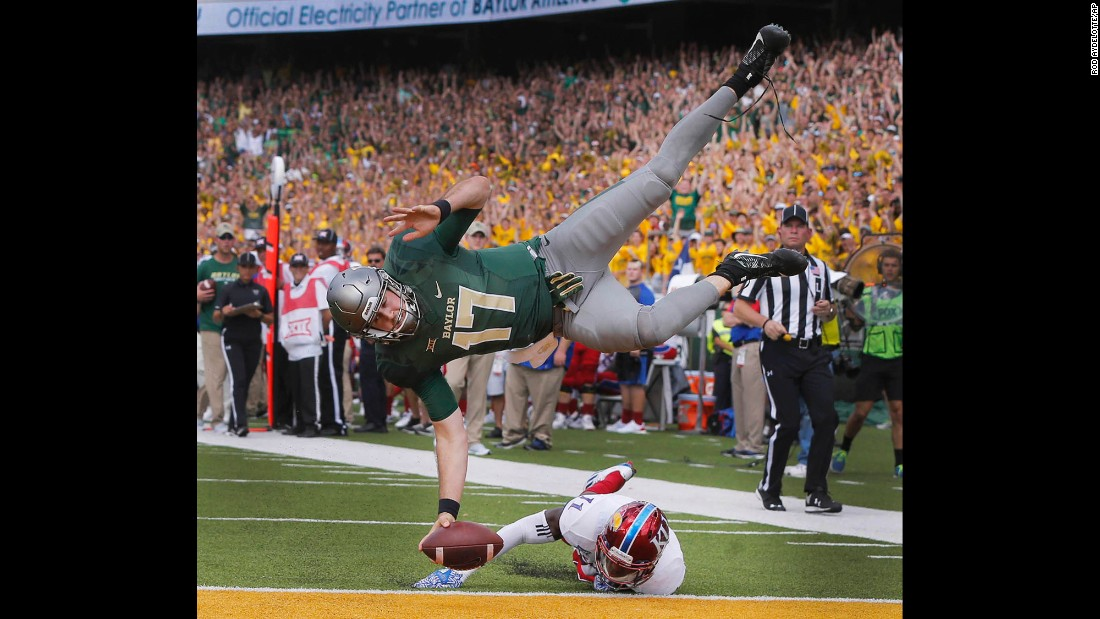 Baylor quarterback Seth Russell scores over Kansas linebacker Mike Lee during a college football game in Waco, Texas, on Saturday, October 15.