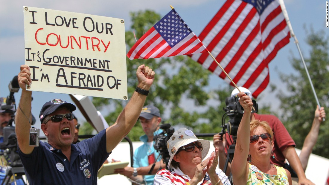"People hold signs and wave flags during the ""Uni-Tea"" tea party rally at Independence Mall in Philadelphia in July 2010. This is the ""love it or leave it"" attitude that has defined traditional patriotism."