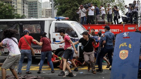 A police van runs over protesters during a protest in front of the US Embassy in Manila.