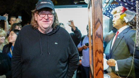 "US filmmaker Michael Moore smiles as he listen to a fortune-telling fairground attraction bearing the likeness of US Republican presidential candidate Donald Trump outside the IFC Theater before attending the debut of a surprise documentary on Trump titled ""TrumpLand"" in New York on October 18, 2016. / AFP / KENA BETANCUR        (Photo credit should read KENA BETANCUR/AFP/Getty Images)"