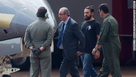 The former president of the Chamber of Deputies Eduardo Cunha (2nd L), is escorted to a Federal Police's plane, departing to Curitiba where he should fulfill his provisionally arrest, which was issued this morning, at the Hangar of the Federal Police in Brasilia on October 19, 2016.  Brazilian police on October 19, 2016 arrested Eduardo Cunha who was one of the country's most powerful lawmakers and the architect of former president Dilma Rousseff's impeachment until engulfed in corruption charges. / AFP / ANDRESSA ANHOLETE        (Photo credit should read ANDRESSA ANHOLETE/AFP/Getty Images)