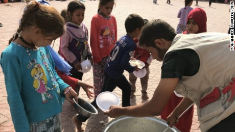 An aid worker hands out dishes of food to displaced Iraqi children at Debaka Camp.