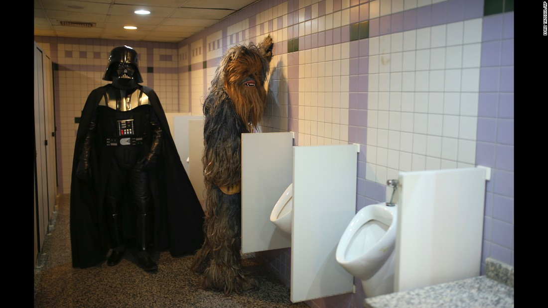 "Fans dressed as ""Star Wars"" characters Darth Vader and Chewbacca use the bathroom during a film festival in Antalya, Turkey, on Monday, October 17."