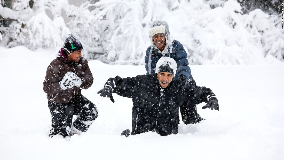 Obama plays with his daughters in the White House Rose Garden during a snowstorm on February 6, 2010.
