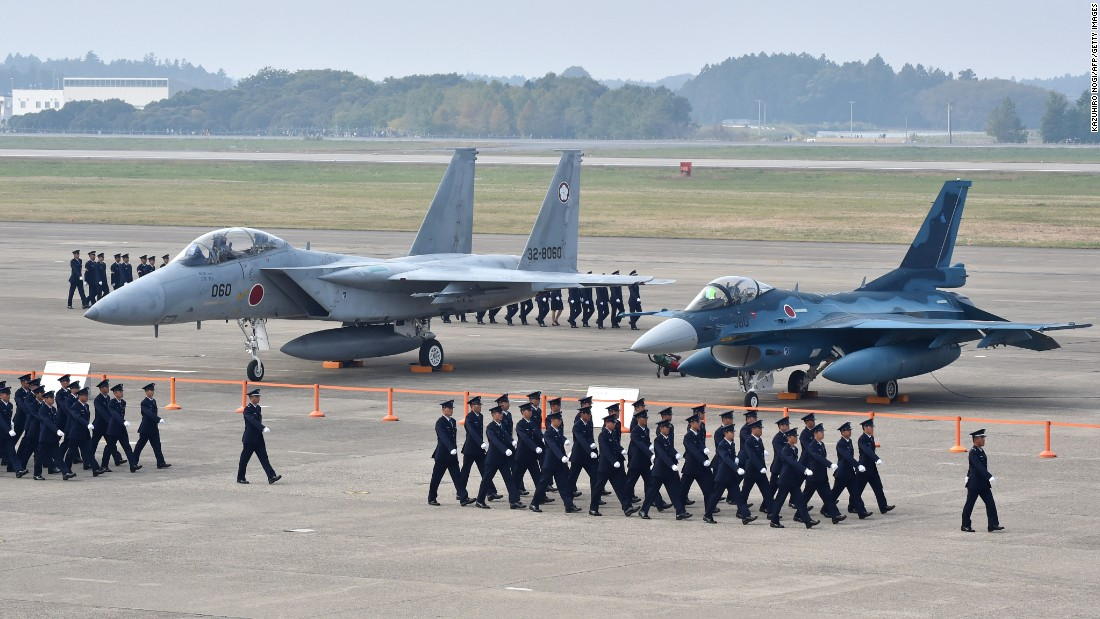 Air servicemen of the Japan Self-Defense Force walk past a F-15J/DJ fighter aircraft (L) and a F-2 A/B fighter aircraft (R) on a runway prior to a review ceremony at the Japan Air Self-Defense Force's Hyakuri air base in Omitama, Ibaraki prefecture on October 26, 2014. Japan has 552 combat capable aircraft.