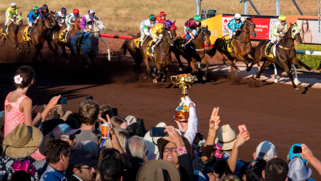 Jockey Cassidy holds the Emirates Melbourne Cup aloft as the 2016 Broome Cup field flash past the winning post at Broome Turf Club, Western Australia.