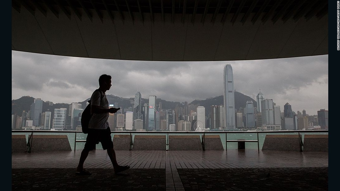 A man walks on a promenade that runs along Victoria Harbor.