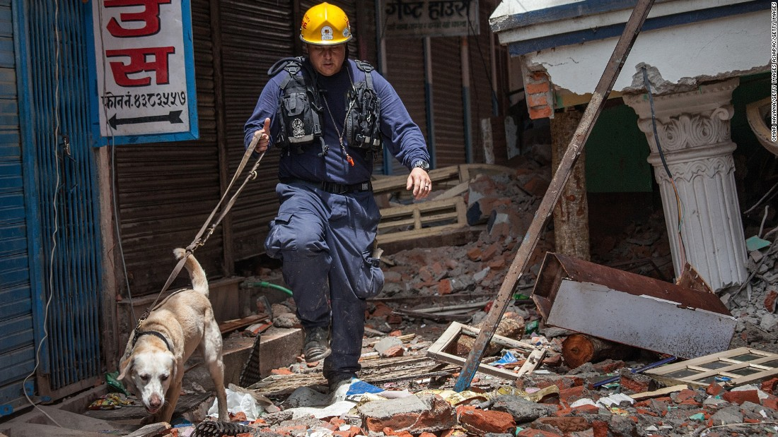 A member of the Los Angeles County Fire Department guides his search dog through a collapsed building on April 30, 2015 in Kathmandu, Nepal.