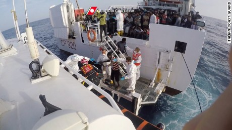 Rescued migrants are transferred from the Italian coast guard ship Gregoretti to a dinghy Friday.
