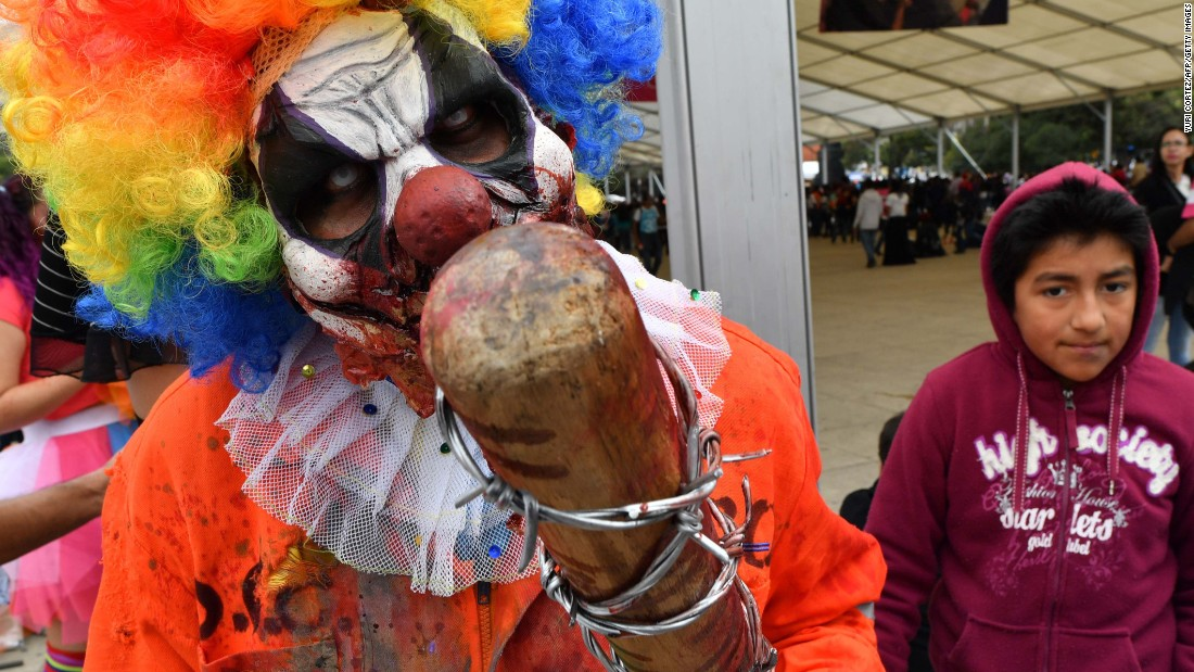 A zombie clown brandishes a baseball bat wrapped in barbed wire.