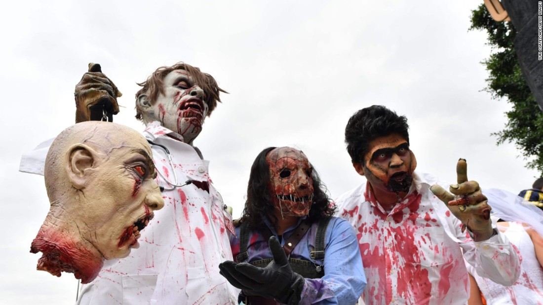 A group of zombies show off their ghoulish prize.
