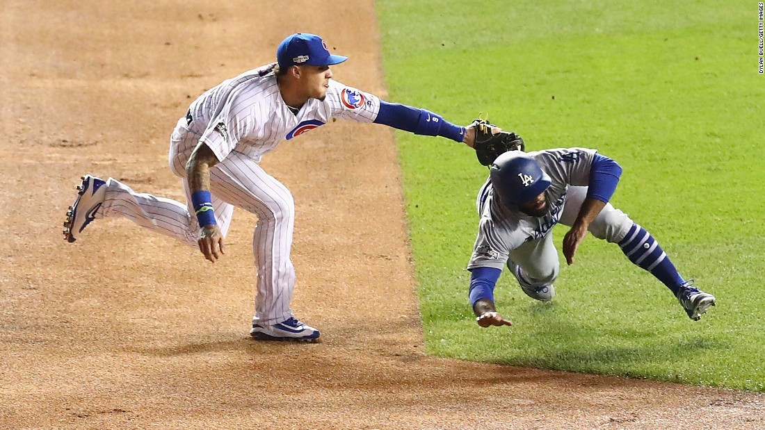 Javier Baez of the Cubs tags out Andrew Toles of the Dodgers at second base in the first inning.
