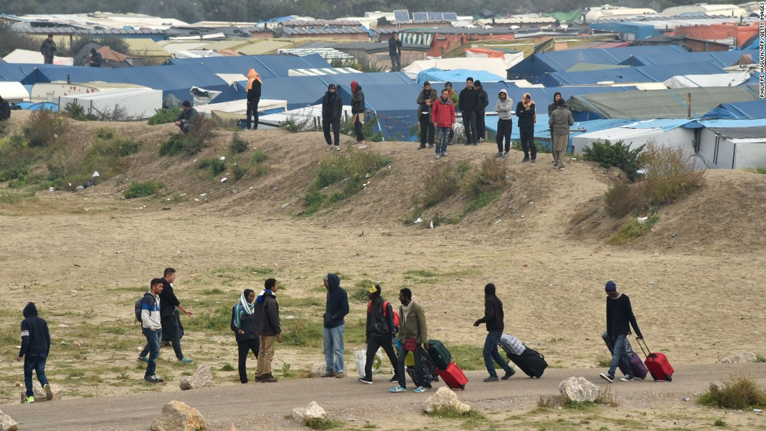 Migrants leave their makeshift homes on October 24.