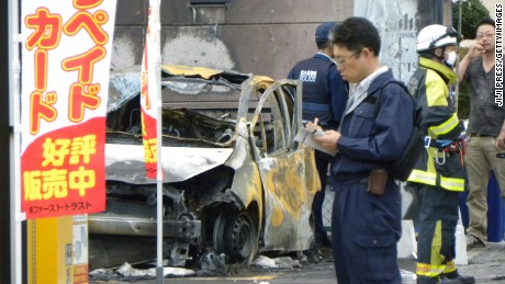 Policemen and firefighters investigate a parking lot after an explosion in Utsunomiya, some 100 kilometres (60 miles) north of Tokyo, on October 23, 2016.
