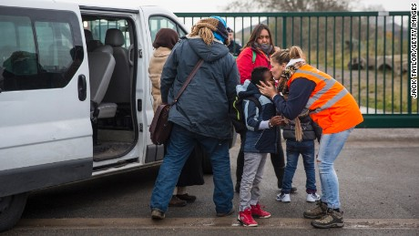 Care workers bring child migrants to a reception point outside the Jungle migrant camp before boarding buses to refugee centers around France.