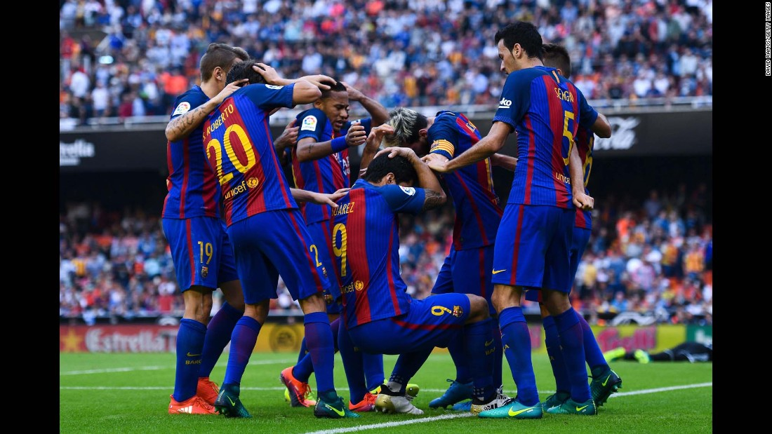 Barcelona players are hit by objects thrown from the crowd after Lionel Messi scored a late penalty to win a league match in Valencia, Spain, on Saturday, October 22.
