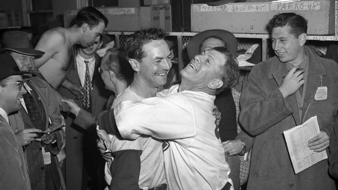 Cubs manager Charlie Grimm, center right, hugs third baseman Stan Hack in the clubhouse after he hit a game-winning double in extra innings to tie the series at three games apiece.