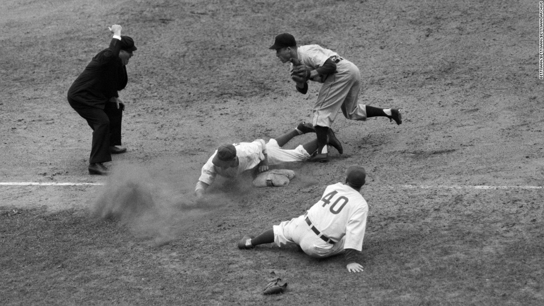 Roy Hughes of the Cubs slides head-first into third base during game six.<br />