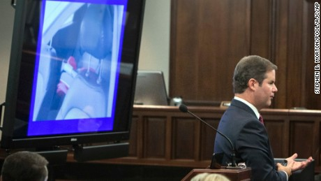 Cobb County Senior Assistant District Attorney Chuck Boring shows the jury a photo of a child's car seat in the back seat of Harris's car.