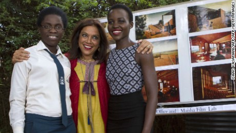 TO GO WITH AFP STORY by Amy Fallon (From R) Mexican-Kenyan Oscar winning actress Lupita Nyongo, Indian film maker Mira Nair and Ugandan national chess champion Phiona Mutesi pose in Kampala on March 28, 2015. Mutesi's tale of triumph over adversity is being turned into a Hollywood epic called 'Queen of Katwe', with Oscar-winning Kenyan actress Lupita Nyong'o tipped to play her mother AFP PHOTO/ ISAAC KASAMANI        (Photo credit should read ISAAC KASAMANI/AFP/Getty Images)