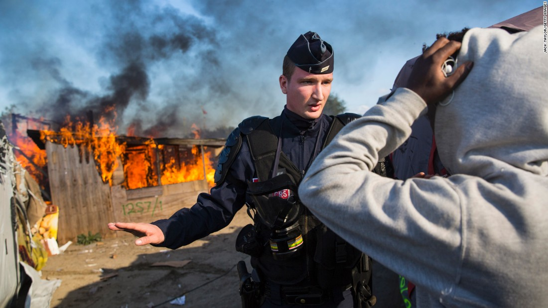 "French authorities stand guard after migrants set fire to a shelter during the dismantling of the Calais ""Jungle"" camp on October 25."