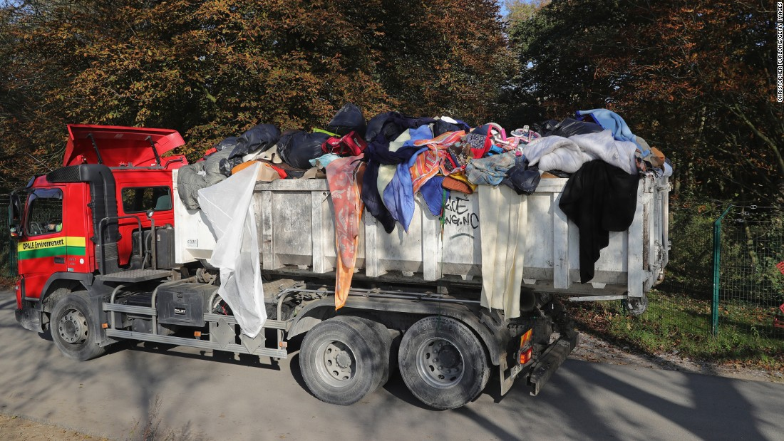 "Migrants' belongings are trucked out of the ""Jungle"" on October 25."
