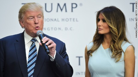 Donald Trump speaks during a ribbon cutting ceremony as his wife Melania looks on at the grand opening of the Trump International Hotel in Washington, DC on October 26, 2016.
