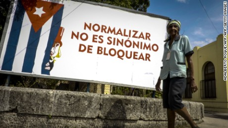 A man passes in front of a poster against the US blockade to Cuba, in Havana on October 26, 2016 after the UN General Assembly adopted a resolution calling for an end to the US embargo against Cuba after the United States for the first time abstained from the vote. The UN General Assembly on Wednesday adopted a resolution calling for an end to the US embargo against Cuba after the United States for the first time abstained from the vote. It was the 25th time that the resolution presented by Cuba was passed, by a vote of 191 countries in favor in the 193-nation assembly. The United States and Israel abstained.  / AFP / Adalberto ROQUE        (Photo credit should read ADALBERTO ROQUE/AFP/Getty Images)