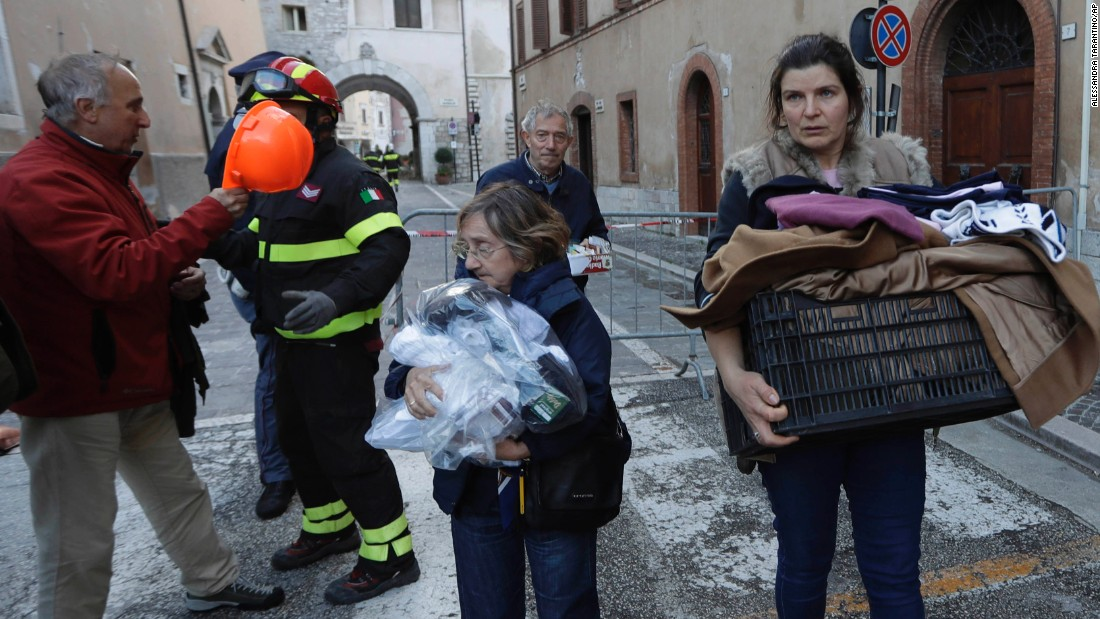 Visso residents carry some of their belongings in the aftermath on October 27.