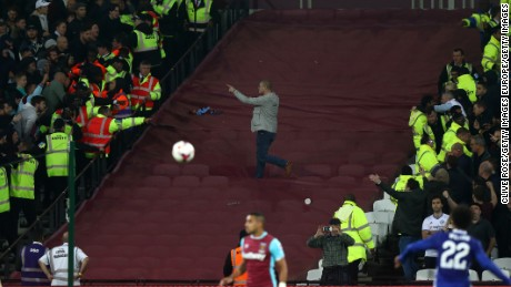 A Chelsea fan gets past the police line and taunts West Ham fans during the EFL Cup clash