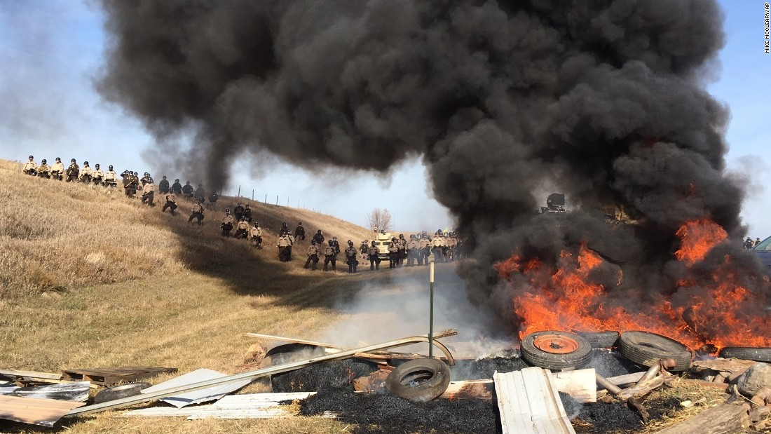 "Tires burn Thursday, October 27, as soldiers and law enforcement officers stand in formation to force protesters off private land where they camped to block construction of the <a href=""http://www.cnn.com/2016/10/27/us/dakota-access-pipeline-protests/"" target=""_blank"">Dakota Access Pipeline. </a>The pipeline is to carry oil from western North Dakota through South Dakota and Iowa to an existing pipeline in Patoka, Illinois."