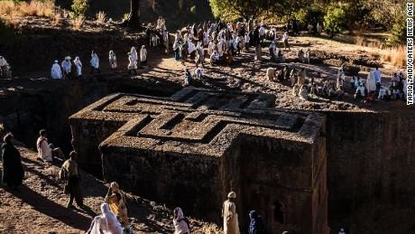 Pilgrims surround the Church of St George in Lalibela, Ethiopia. Shaped like a Greek Orthodox cross, the Church of St George is perhaps the most famous of Lalibela's 13 churches. It was painstakingly excavated out of the rock, some 40 feet down, with hammer and chisel and built after King Lalibela's death by his widow as a memorial.