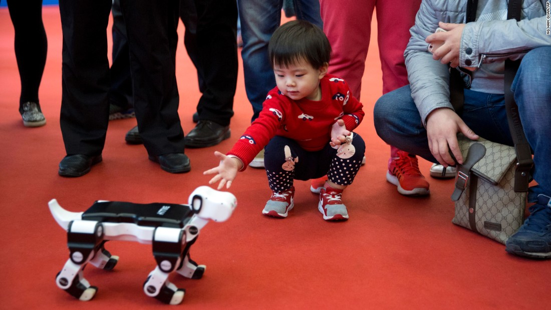 A child reaches out to a robotic dog at the World Robot Conference in Beijing on Friday, October 21.