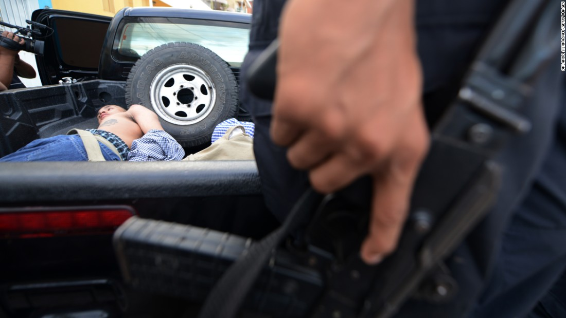 A suspected gang member is held in custody during a police raid in Tegucigalpa, Honduras, on Monday, October 24.