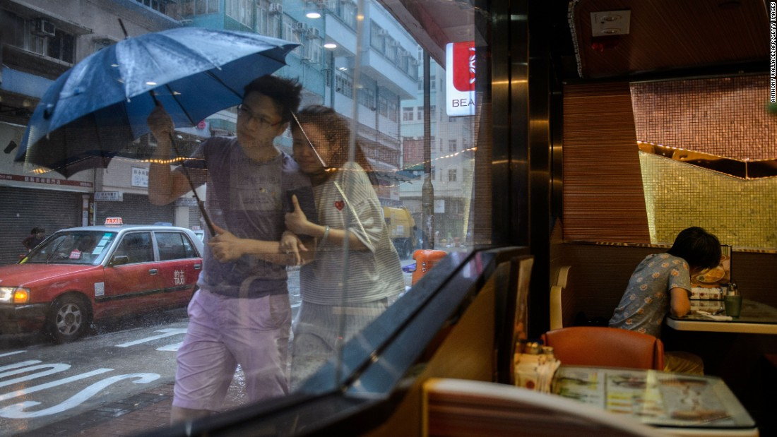 "A couple walk in heavy rain as Typhoon Haima <a href=""http://www.cnn.com/2016/10/20/asia/hong-kong-typhoon-haima/"" target=""_blank"">made landfall in Hong Kong</a> on Friday, October 21."