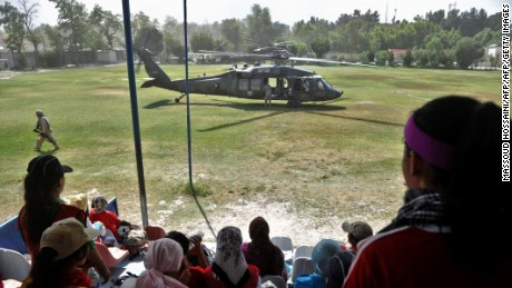 Afghanistan's women's national football team members take a break from training as a US Black Hawk helicopter lands.