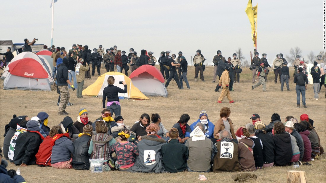 Pipeline protesters sit in a prayer circle as a line of law enforcement officers make their way across the camp to relocate the protesters a few miles south on Thursday, October 27. Protesters had camped on private property.