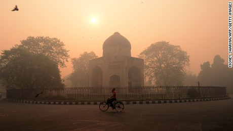 "TOPSHOT - An Indian cyclist rides along a street as smog envelops a monument in New Delhi on October 31, 2016, the day after the Diwali festival. New Delhi was shrouded in a thick blanket of toxic smog a day after millions of Indians lit firecrackers to mark the Diwali festival, causing the air pollution to hit ""severe"" level. The pollutants breached the 1000 microgram mark in the Indian capital and shot up nearly 10 times above the normal level in  the early hours of Monday, mostly owing to bursting of millions of firecrackers, according to a weather scientist.  / AFP / MONEY SHARMA        (Photo credit should read MONEY SHARMA/AFP/Getty Images)"