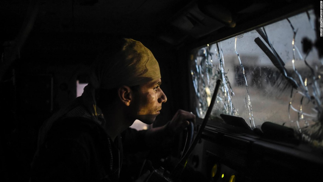 An Iraqi soldier navigates through a shattered windshield as coalition forces advance on Bazwaya on October 31.