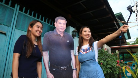 Visitors pose with a life-size picture of  Philippine President Rodrigo Duterte, in front of his house in Davao on Oct.22, 2016.( The Yomiuri Shimbun via AP Images )