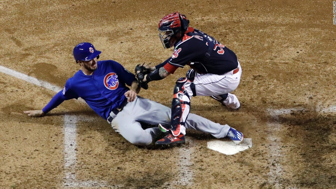 Kris Bryant of the Cubs slides safely under Indians catcher Roberto Perez during the fourth inning of Game 7.