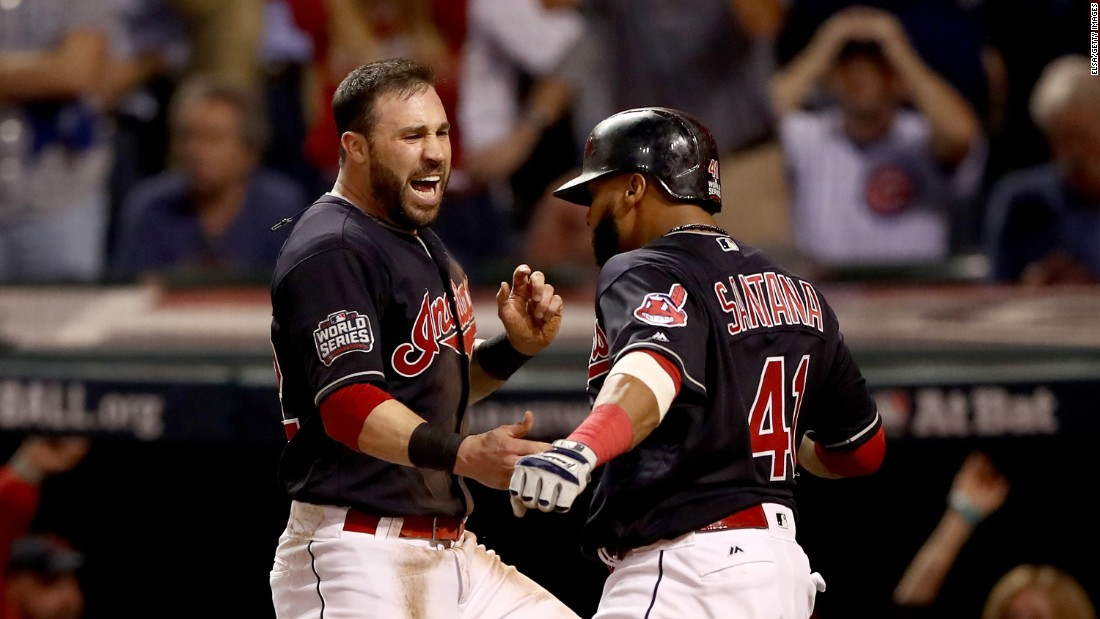 Jason Kipnis  and Carlos Santana of the Cleveland Indians celebrate after scoring runs on a wild pitch during the fifth inning in Game 7.